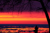 Don Campbell / H-P staff A photographer takes advantage of Tuesday night's sunset, as well as the remaining ice in Lake Michigan along Silver Beach in St. Joseph.