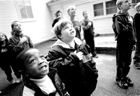 Six-year-old Stephon Willis, left, a first grade student at Wood School joins classmates in reciting the Pledge of Allegiance, Wednesday morning, prior to the start of school. Each morning, the 15 stu