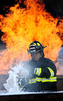Don Campbell / H-P staff Benton Harbor Public Safety Officer Jared Graves demonstrates the use of compressed air foam to extinguish a controlled fire during a town hall meeting Wednesday, August 31, 2